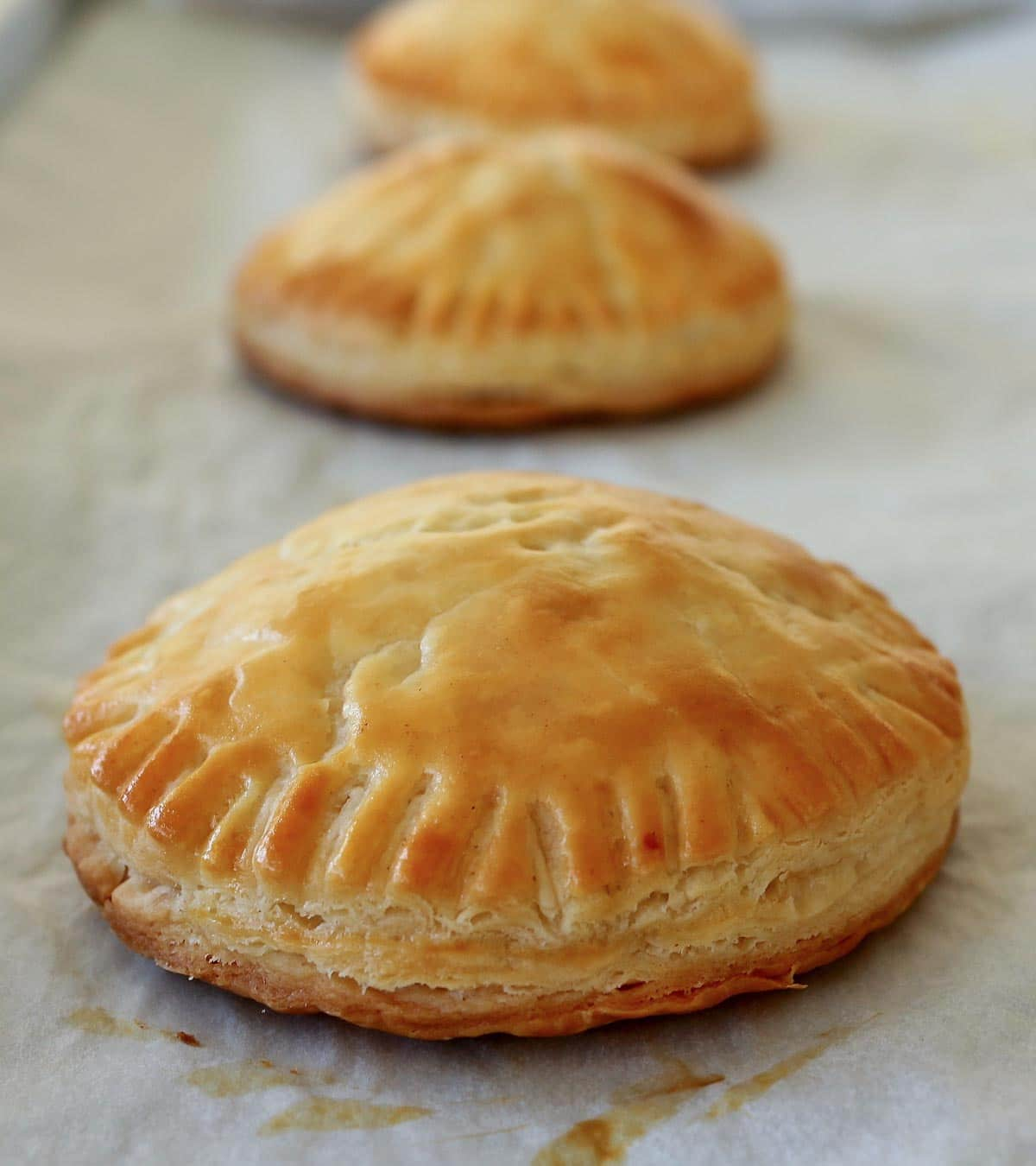 Closeup of a row of round baked empanadas on a baking sheet.