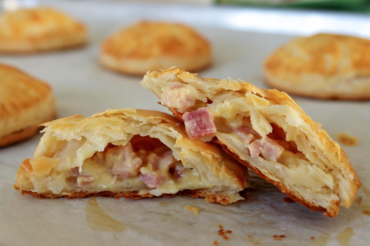 Baked ham and cheese empanadas on a baking sheet with one broken in half.