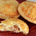 Two and a half round ham and cheese empanadas on a square dark red plate.