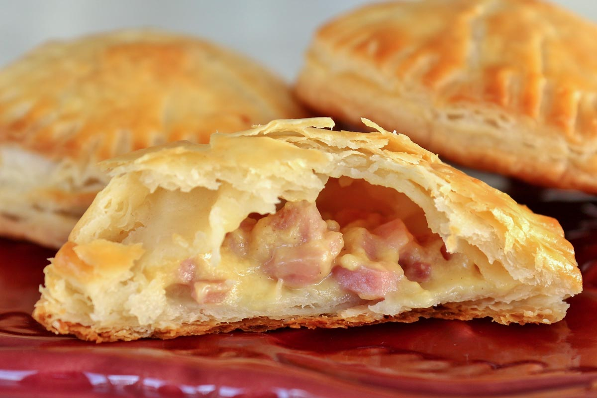 Closeup of a cross-section of a ham and cheese empanada showing off the filling.