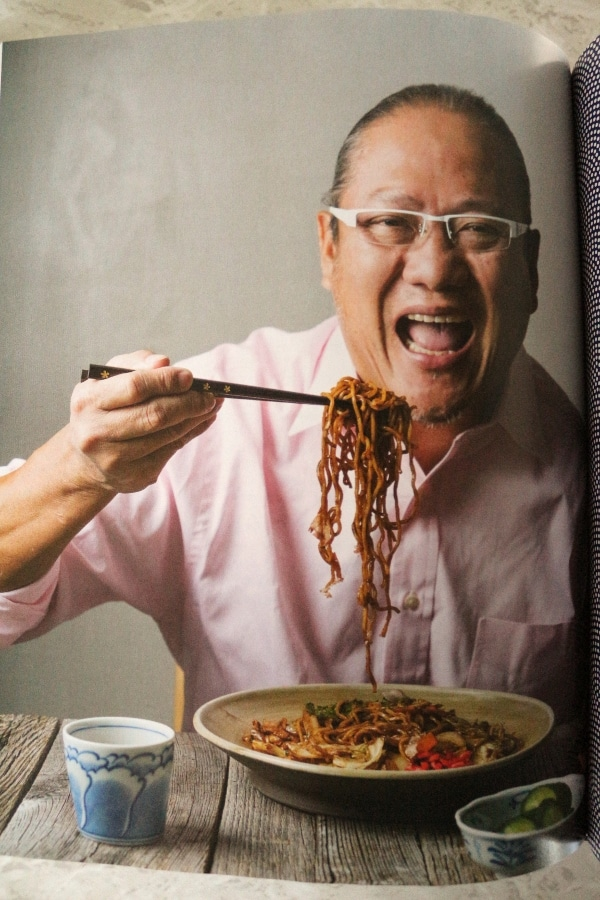 Masaharu Morimoto holding holding chopsticks with noodles up to his mouth