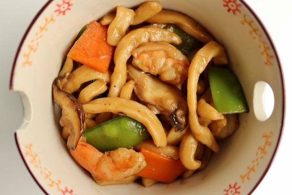 overhead closeup of a bowl of stir-fried udon noodles with shrimp and vegetables