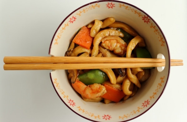 overhead view of a bowl of yaki udon with chopsticks balanced on top