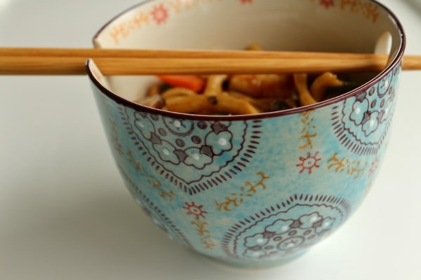 a pretty blue bowl of food with chopsticks balanced on top