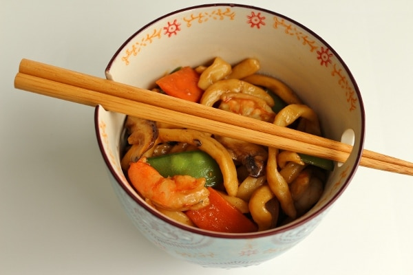 yaki udon noodles with seafood in a small Asian style bowl with chopsticks