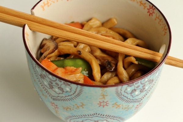 side view of a bowl of yaki udon with chopsticks balanced on top
