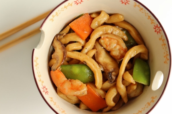 a closeup of a small bowl of yaki udon noodles with seafood and vegetables