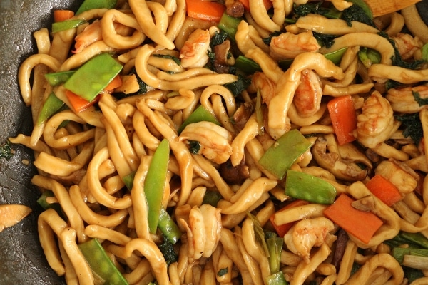 stir-fried yaki udon noodles with shrimp and vegetables in a wok