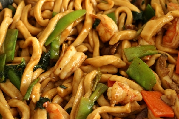 a closeup of a wok filled with stir-fried yaki udon with shrimp and vegetables
