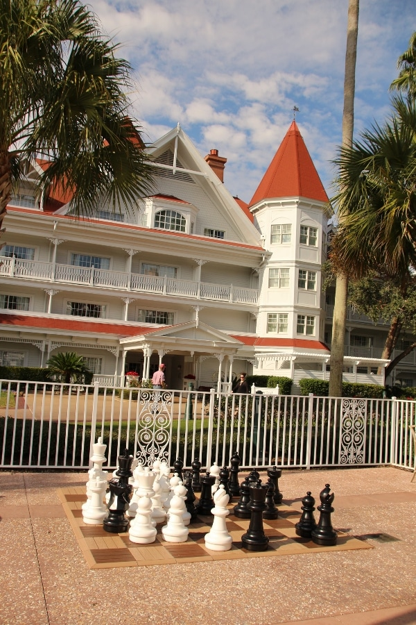 a large chess set built into the ground, in front of a large building