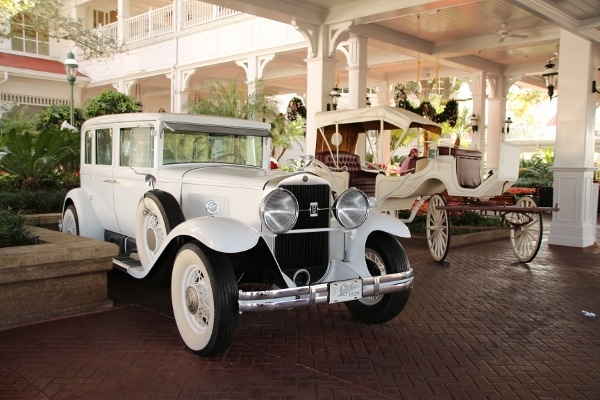 two white antique cars outside Disney\'s Grand Floridian Resort