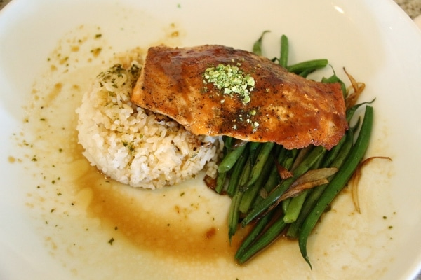 a salmon fillet served with rice and green beans on a white plate