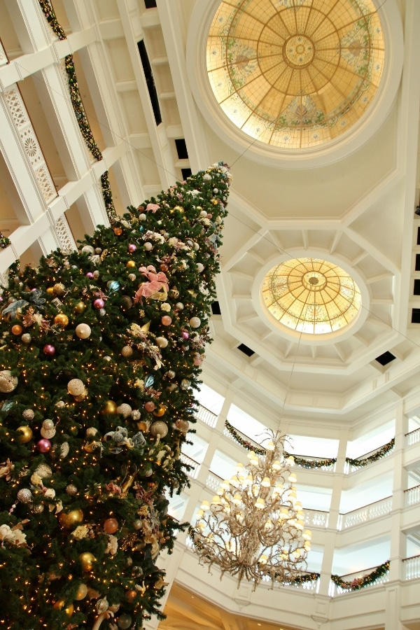 view looking up at a tall Christmas tree in a vast hotel lobby