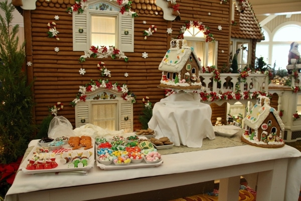 a wide view of a gingerbread house display with trays of candy for decorating
