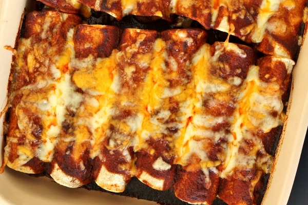 overhead view of a casserole of enchiladas with bubbly cheese