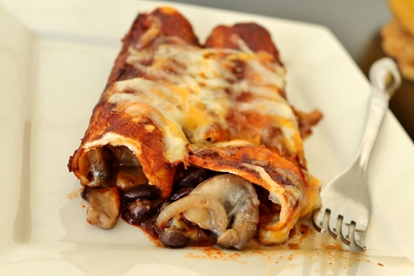 a closeup of enchiladas on a plate showing the mushroom and black bean filling