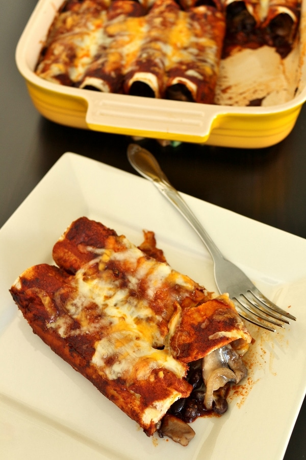 A plate of enchiladas with a casserole dish in the background