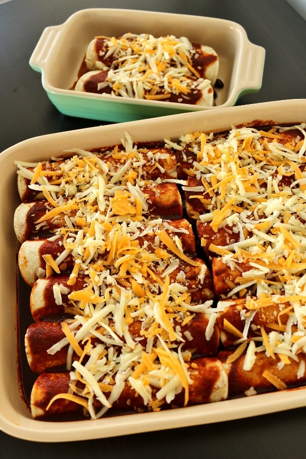 unbaked casserole dishes filled with enchiladas topped with cheese