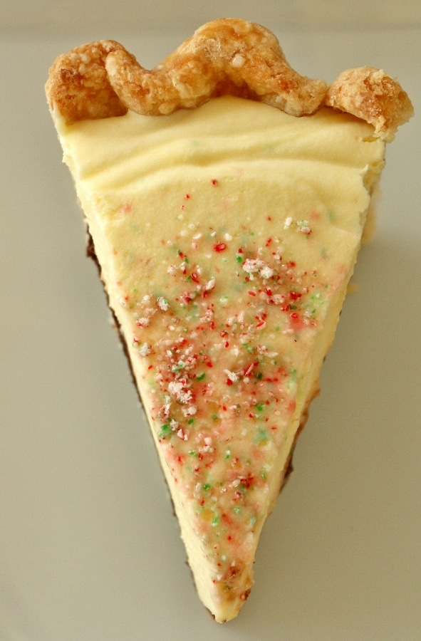 overhead view of a slice of creamy pie topped with crushed peppermint candies