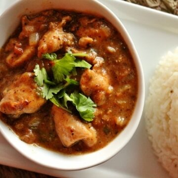 Cape Malay chicken curry in a small white bowl with a scoop of basmati rice