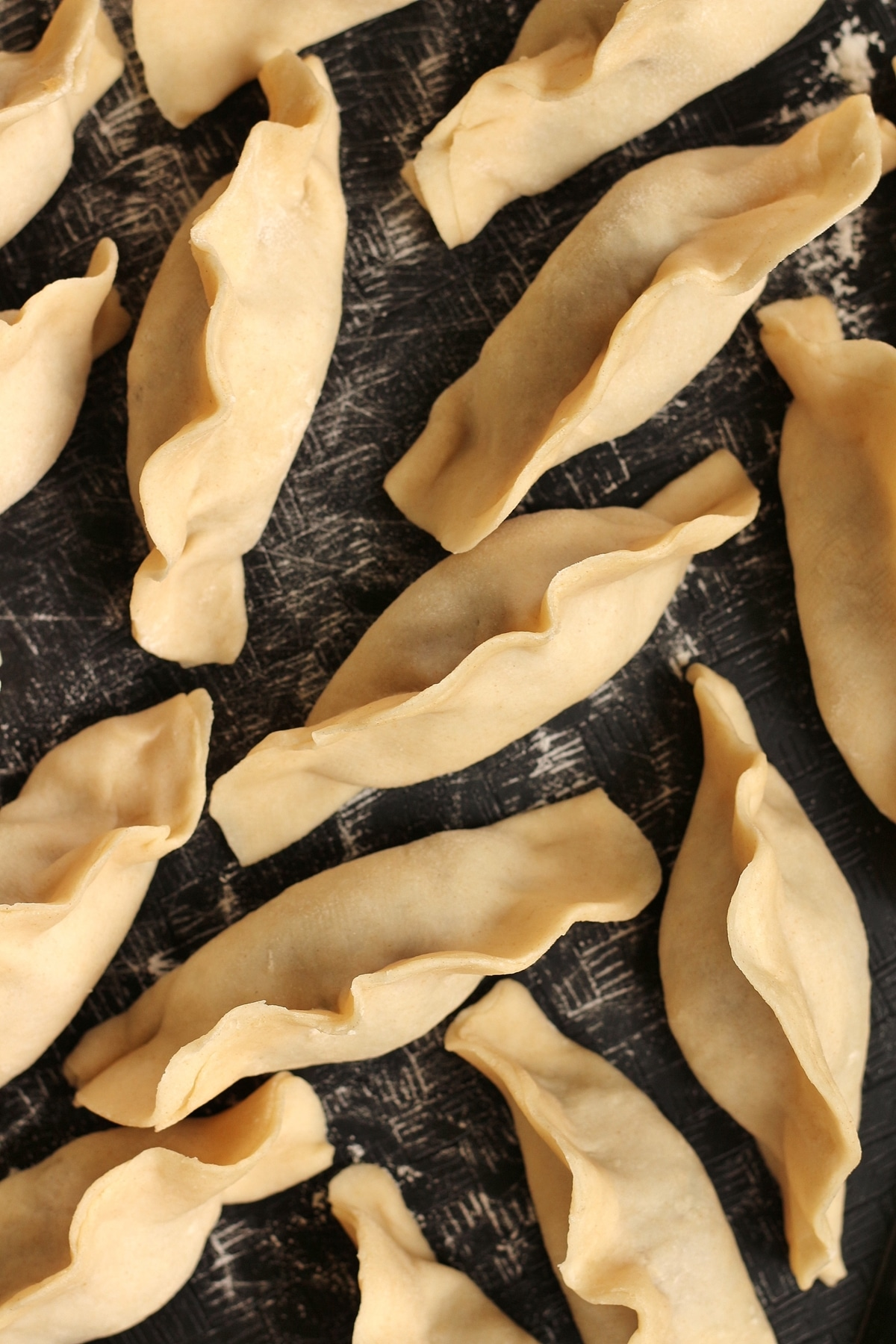 overhead view of uncooked Chinese dumplings on a black surface