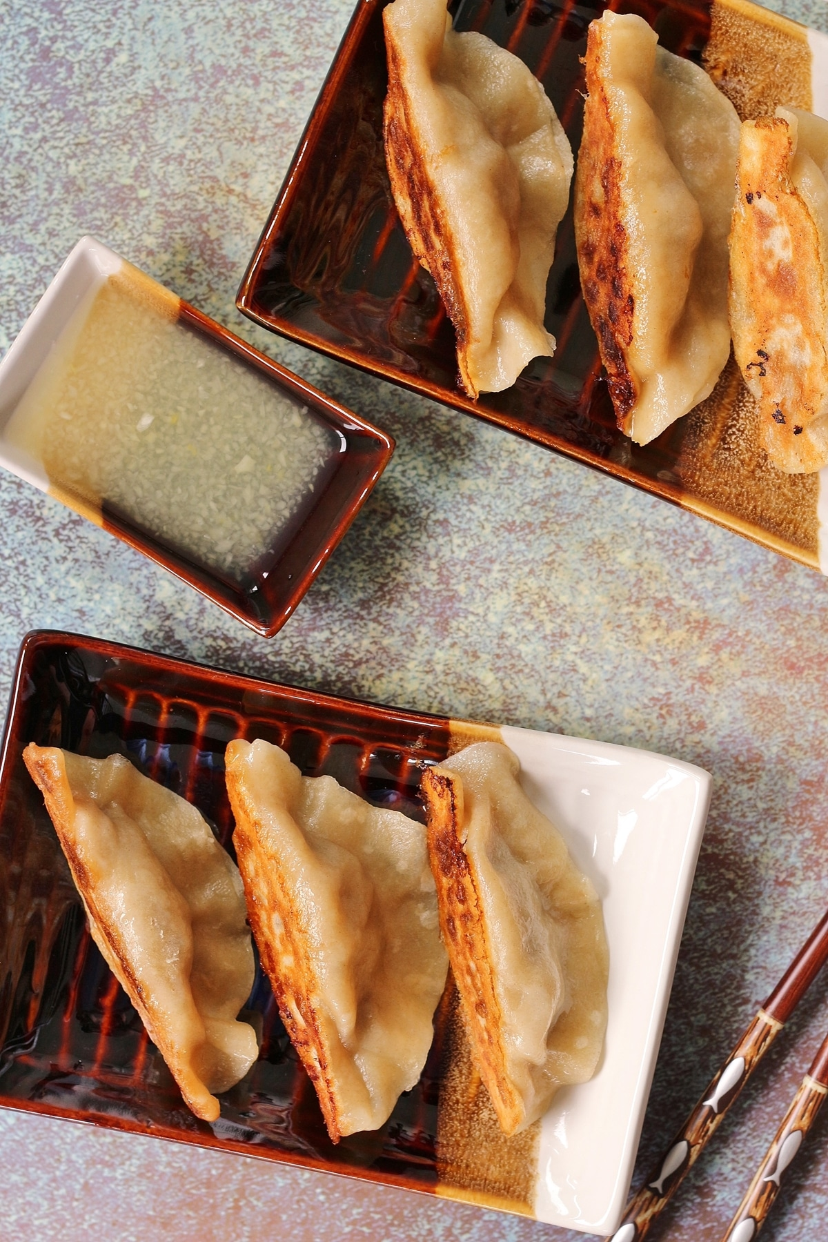 overhead view of two small rectangular plates of pan-fried spicy beef dumplings