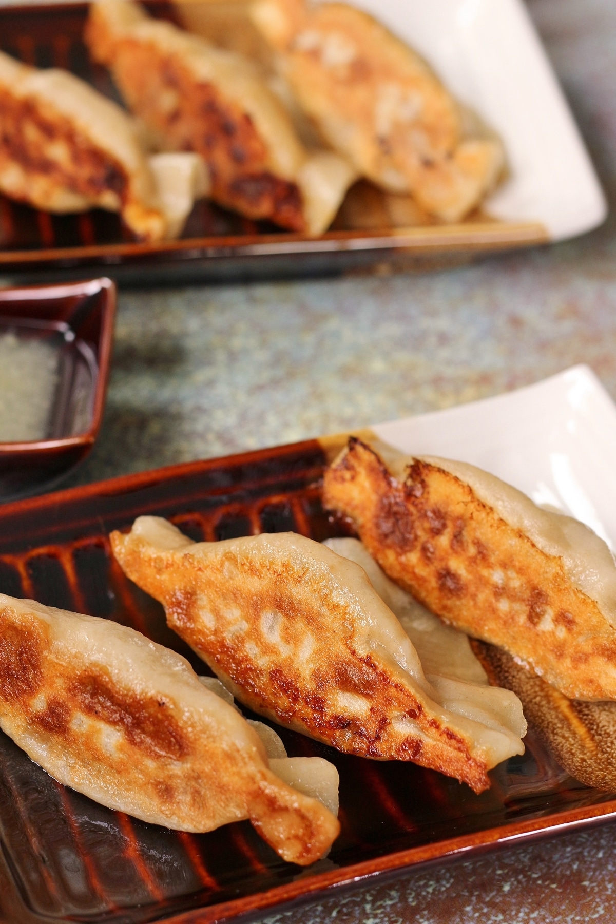 two small rectangular plates of pan-fried Chinese dumplings showing off their crispy bottoms