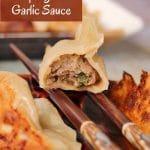a closeup of a half-eaten beef dumpling resting on two chopsticks