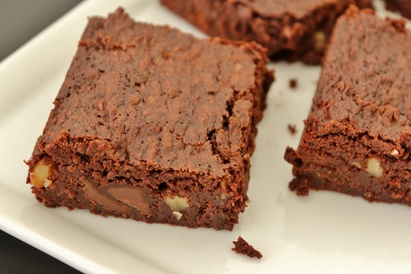 closeup of a plate of brownies made with chocolate chips and walnuts