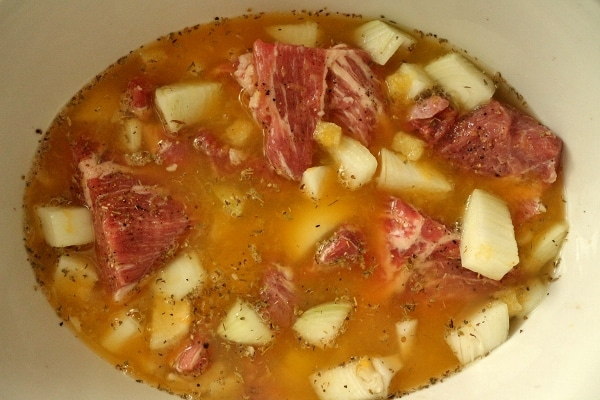 big cubes of pork with onions and liquid in a slow cooker