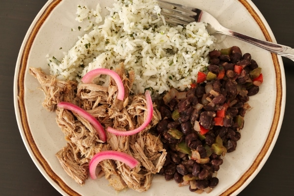overhead view of a plate of slow-cooked mojo pork with black beans and rice
