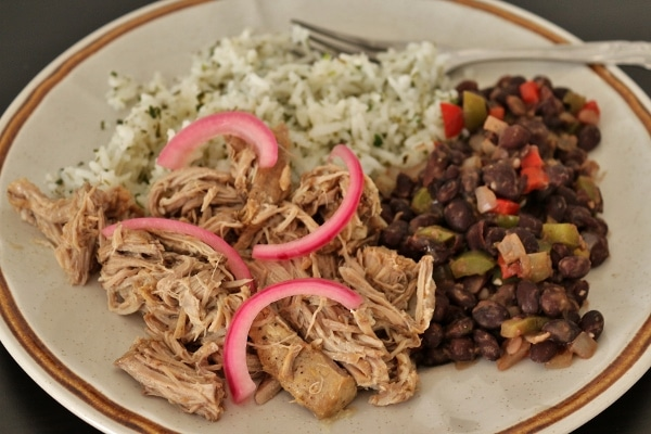 side view of a plate of pulled mojo pork with beans and rice