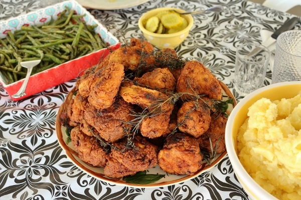 a big platter of fried chicken flanked by bowls of green beans and mashed potatoes