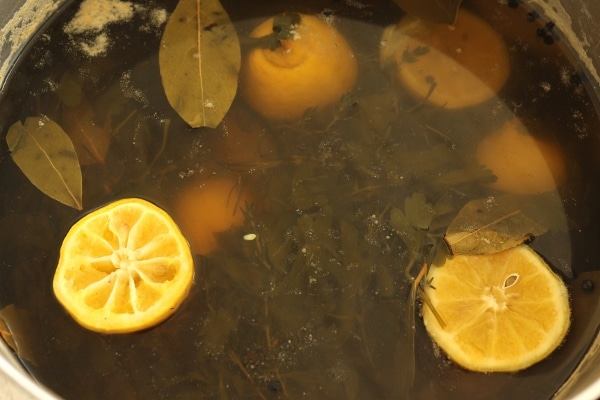a pot of brine with lemons and herbs