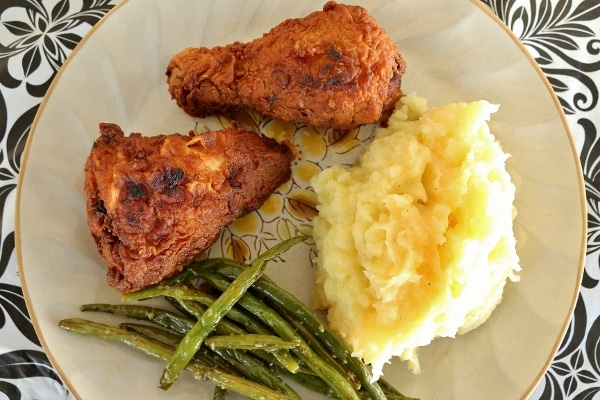 overhead view of a plate of fried chicken with mashed potatoes and green beans
