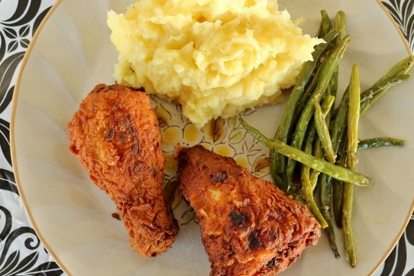 overhead view of a plate of fried chicken with green beans and mashed potatoes