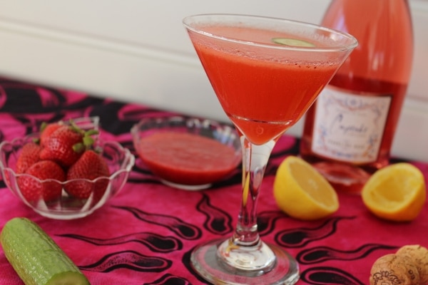 a bright pink cocktail, cucumber, bowl of strawberries, and halved lemon