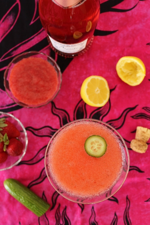 overhead view of a pink cocktail next to lemons and a bowl of strawberries