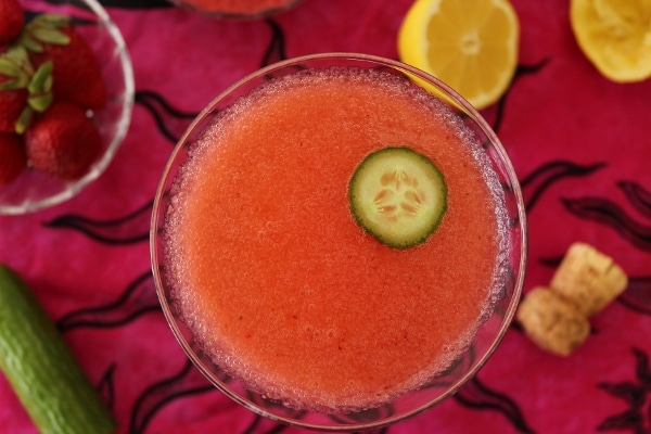 overhead view of a pink cocktail with a slice of cucumber floating on top