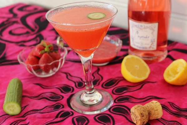 a pink cocktail on a pink tablecloth topped with various ingredients