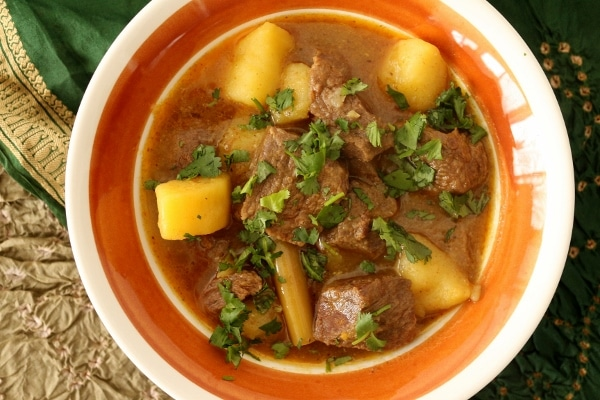 A bowl of Burmese beef curry with big cubes of potatoes, and chopped cilantro garnish