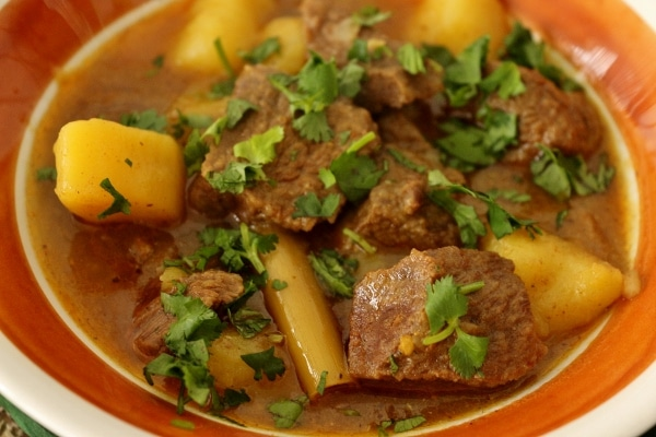 A close up of a bowl of Burmese beef curry with big cubes of potatoes, and chopped cilantro garnish