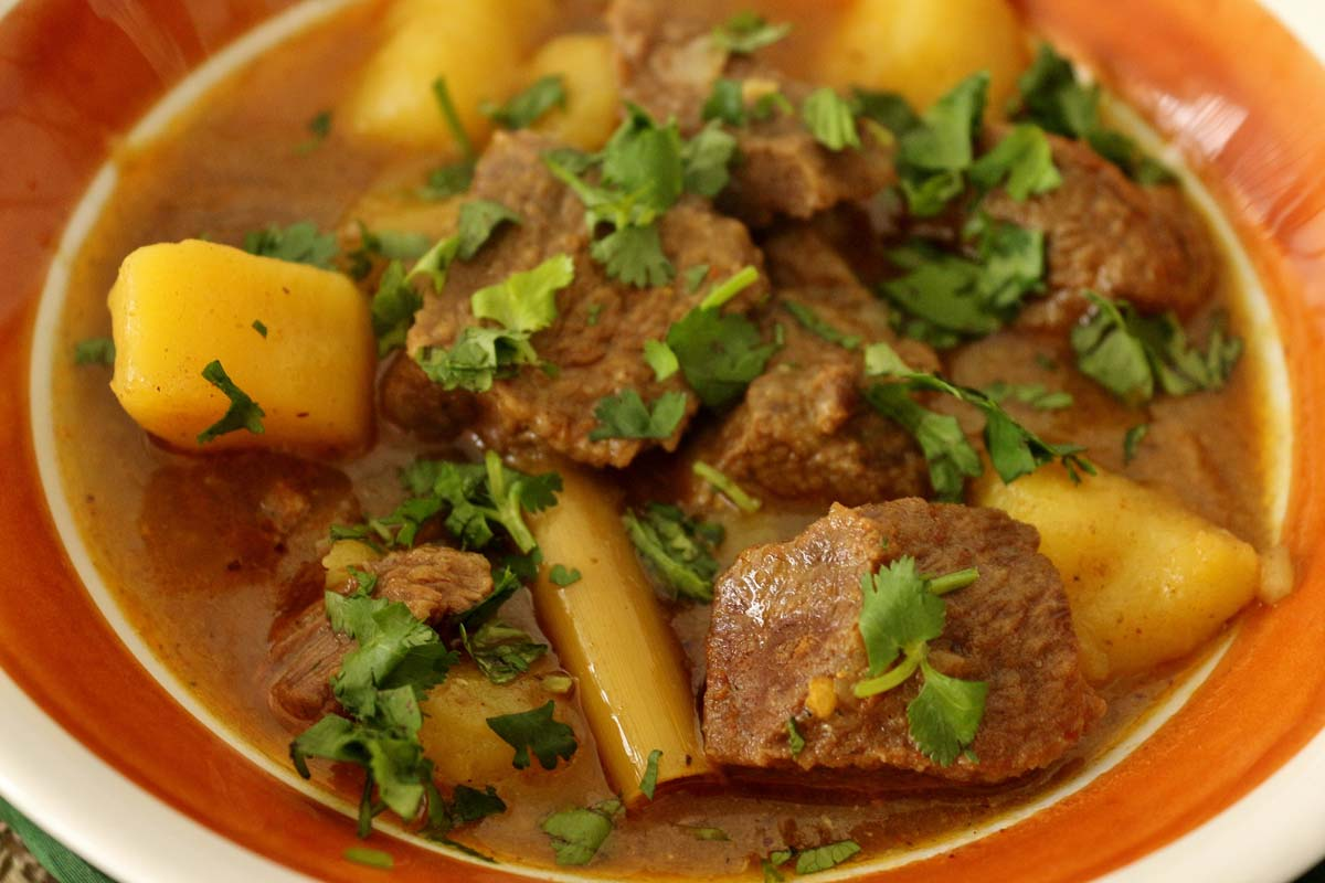 A close up Burmese beef curry with potatoes in an retro brown and white bowl.