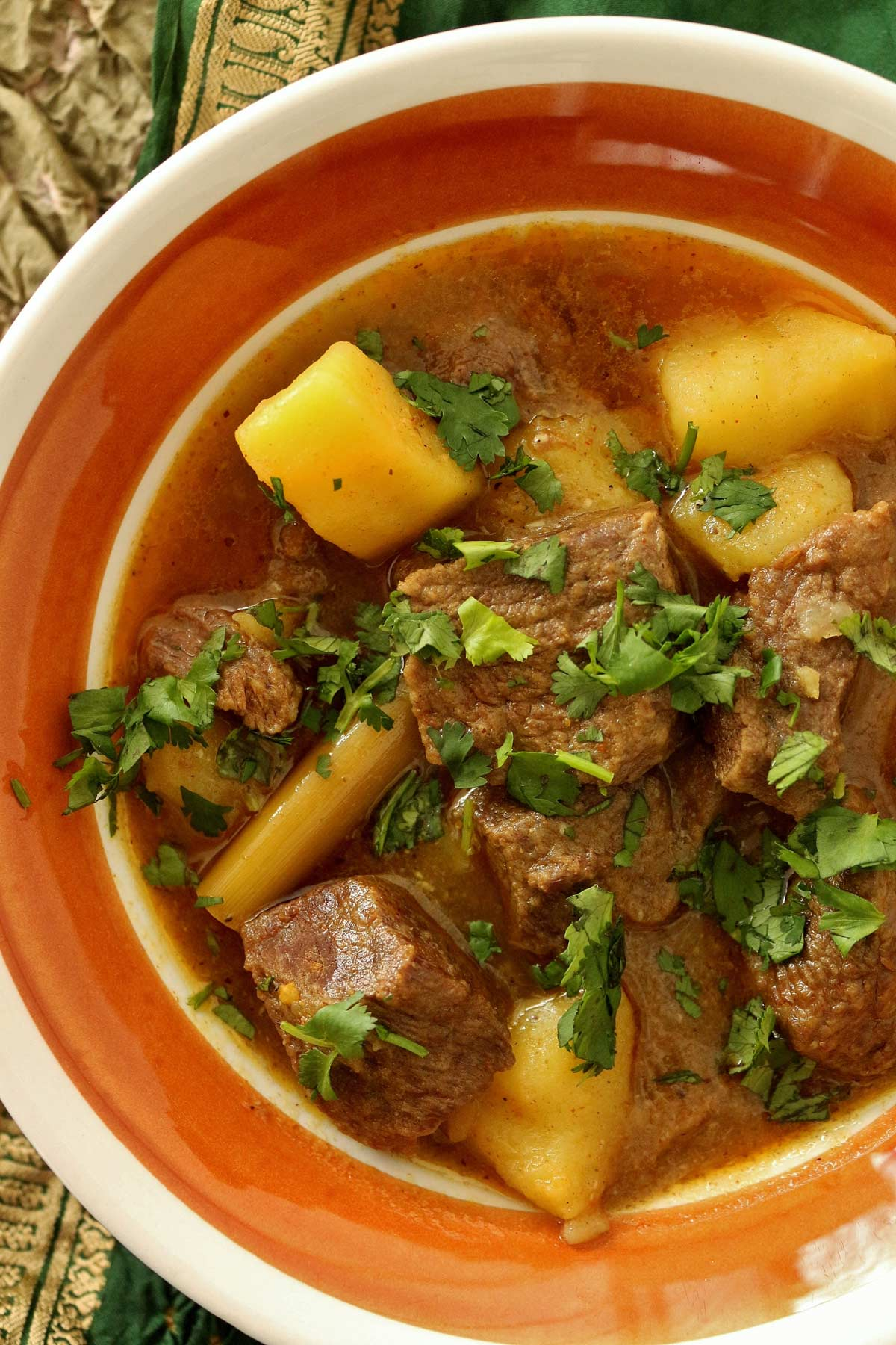 A close up of Burmese beef curry with potatoes, garnished with cilantro.