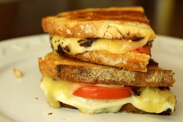 stacked sandwich halves with melted cheese, tomato, and olive tapenade