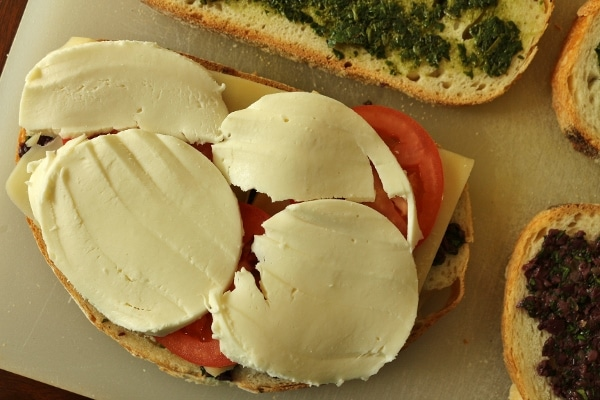assembling a sandwich with sliced mozzarella, tomatoes, and pesto