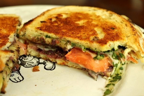 a closeup of a half eaten sandwich with pesto and tomatoes inside