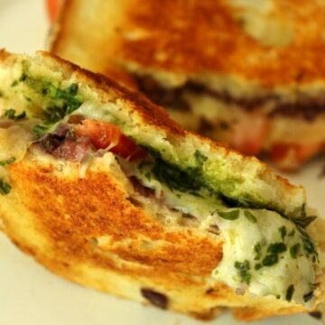 A close up of a half eaten sandwich with pesto inside