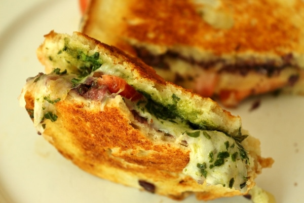 A close up of a half eaten grilled cheese with tomatoes and pesto inside