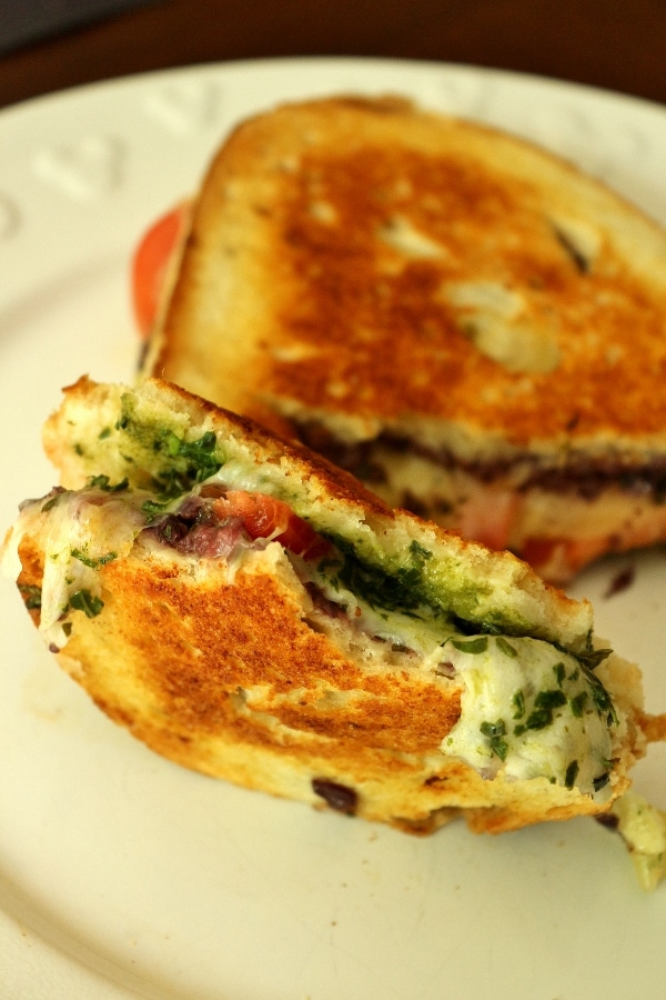 A close up of a half eaten grilled cheese with pesto inside